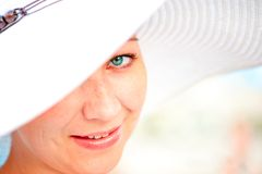 一个年轻迷人的微笑的女孩的特写镜头画象帽子的 免版税库存图片