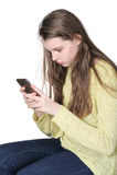 一个年轻逗人喜爱的女孩神色严密地到她的智能手机里 库存图片