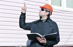 一个建造场所的工作者在冬天看图画 库存图片