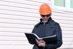 一个建造场所的工作者在冬天看图画 免版税图库摄影