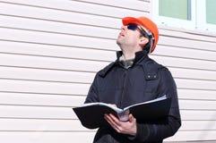 一个建造场所的工作者在冬天看图画 免版税库存图片