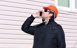一个建造场所的工作者在冬天谈话在智能手机 图库摄影