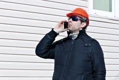 一个建造场所的工作者在冬天谈话在智能手机 免版税库存图片