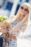 一个年轻金发碧眼的女人的画象有一个手机的 库存图片