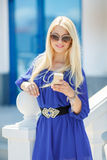 一个年轻金发碧眼的女人的画象有一个手机的 库存照片