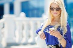 一个年轻金发碧眼的女人的画象有一个手机的 免版税库存图片