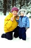 一个年长妇女和孩子在冬天森林里 库存照片