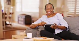 一个年长黑人妇女愉快地使用她的片剂,当看照相机时 库存图片