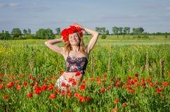 一个年轻,愉快,美丽的女孩获得乐趣并且跳舞充满在开花的鸦片的领域的喜悦与鸦片花花圈的  免版税库存照片