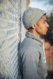 一个年轻,熟悉内情的人为沿篱芭的一张沉思画象摆在N 库存图片