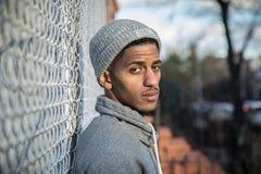 一个年轻,熟悉内情的人为沿篱芭的一张沉思画象摆在N 图库摄影