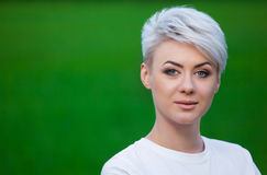 一个年轻,美丽,微笑的女孩的画象有短发的金发碧眼的女人 免版税图库摄影