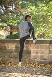 一个年轻,运动人在公园舒展在奔跑- Autum前 免版税库存照片