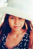 一个beautifull亚裔女孩的画象有白色帽子的在海滩的暑假 库存照片