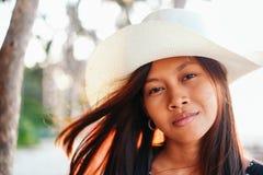 一个beautifull亚裔女孩的画象有白色帽子的在海滩的暑假 库存图片