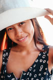 一个beautifull亚裔女孩的画象有白色帽子的在海滩的暑假 图库摄影