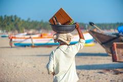 一个goan人运载的篮子充分在他的头上面的果子  免版税库存照片