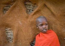 一个Maasai男孩的画象传统礼服的在房子附近 库存照片