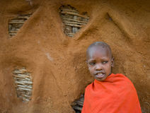 一个Maasai男孩的画象传统礼服的在房子附近 免版税库存图片
