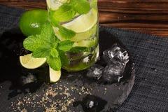 一个mojito鸡尾酒的特写镜头在一个黑色的盘子的 在木背景的绿色mojito 绿色石灰薄菏、片断和冰块 库存照片