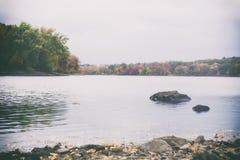 一个New England湖和森林的一张减速火箭的影片样式照片秋天的 免版税库存照片