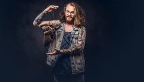 一个tattoed红头发人行家男性的画象与长的丰富的在T恤杉和夹克举行穿戴的头发和充分的胡子的 免版税图库摄影