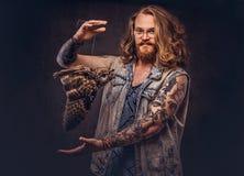 一个tattoed红头发人行家男性的画象与长的丰富的在T恤杉和夹克举行穿戴的头发和充分的胡子的 免版税库存照片