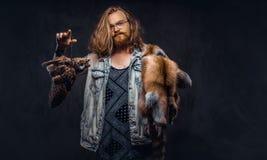 一个tattoed红头发人行家男性的画象与长的丰富的在T恤杉和夹克举行穿戴的头发和充分的胡子的 免版税库存图片
