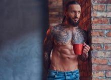 一个tattoed赤裸上身的男性的画象与一个时髦的理发和胡子,饮料早晨咖啡的,倾斜反对砖 免版税库存图片