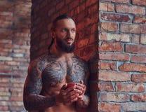 一个tattoed赤裸上身的男性的画象与一个时髦的理发和胡子,饮料早晨咖啡的,倾斜反对砖 库存图片