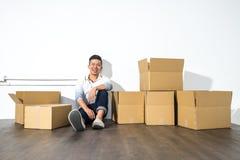 一个yong亚裔人坐微笑与箱子的地板 库存图片