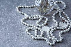 一串珍珠和香水在石背景 图库摄影