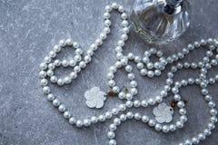 一串珍珠和香水在石背景 免版税库存图片