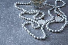 一串珍珠和香水在石背景 免版税库存照片