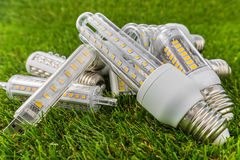 一些个E27、USB和R7s LED电灯泡在草 免版税库存照片