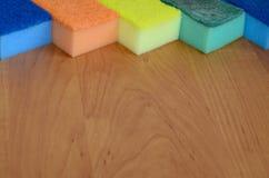 一些块厨房海绵在一个木厨房工作台面说谎 洗涤的盘的五颜六色的对象和清洗在房子准备好 免版税库存照片