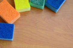 一些块厨房海绵在一个木厨房工作台面说谎 洗涤的盘的五颜六色的对象和清洗在房子准备好 免版税图库摄影