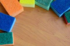 一些块厨房海绵在一个木厨房工作台面说谎 洗涤的盘的五颜六色的对象和清洗在房子准备好 库存图片