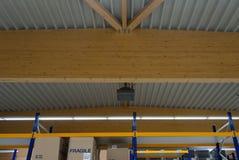 一些大木捆支持一排大工厂厂房的屋顶 库存照片