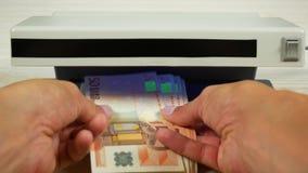 一些欧元笔记在手中 检查货币探测器 股票视频