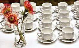 一些空的茶或咖啡杯和在空白表的花瓶 免版税库存照片