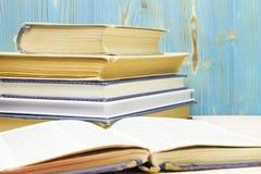 一些非常老使用的精装书书或课本和新书堆在图书馆里 免版税库存照片