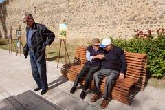 一些年长人谈话激动在乔治亚老镇街道长凳的  库存图片