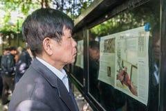 一人读书报纸福兴公园上海瓷 免版税库存图片