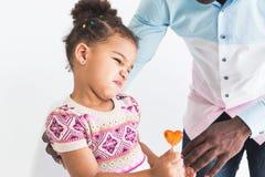 一件五颜六色的礼服和她的爸爸的淘气女孩白色背景的 免版税库存图片
