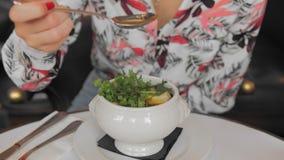 一件五颜六色的衬衣的未被认出的法国妇女吃与匙子的传统法国葱汤 慢动作,特写镜头 影视素材