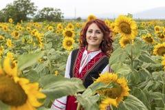 一件传统保加利亚礼服的女孩在向日葵的领域 免版税库存照片
