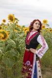 一件传统保加利亚礼服的女孩在向日葵的领域 免版税图库摄影