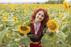 一件传统保加利亚礼服的女孩在向日葵的领域 库存照片
