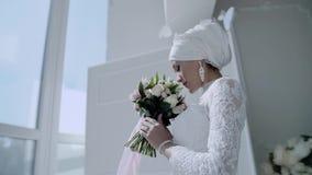 一件全国白色礼服的一美丽的美丽的少女站立与花束靠近一个轻的窗口和神色在b 股票录像